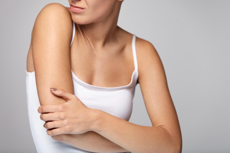 Thrombose im Arm: Frau hält ihren Arm fest