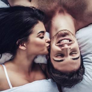 Horoskop: Eine Frau gibt ihrem Partner im Bett einen Kuss auf die Wange
