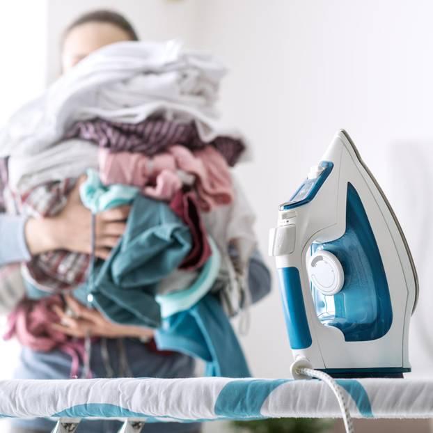 Frau mit Bügelwäsche steht am Bügelbrett