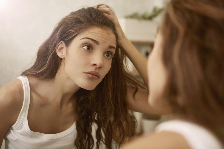Pickel ausdrücken: Junge Frau schaut besorgt in den Spiegel und hält ihre Haare dabei aus dem Gesicht
