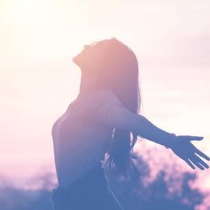 Horoskop: Eine Frau genießt den Sonnenuntergang