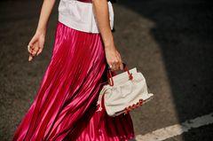 Plisséerock: roter Rock mit Handtasche