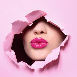 pinker Lippenstift: Gesicht mit pinkem Lippenstift durch eine Paierwand