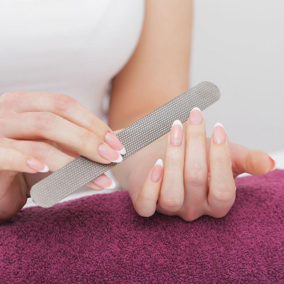 Stiletto Nägel: Frau feilt sich die Fingernägel