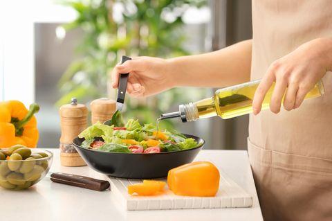 Fette Irrtümer: Frau gießt Olivenöl in Salat