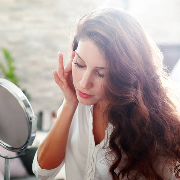 Pickel im Ohr: Frau fasst sich vor das rechte Ohr und blickt Richtung Spiegel auf einem Tisch