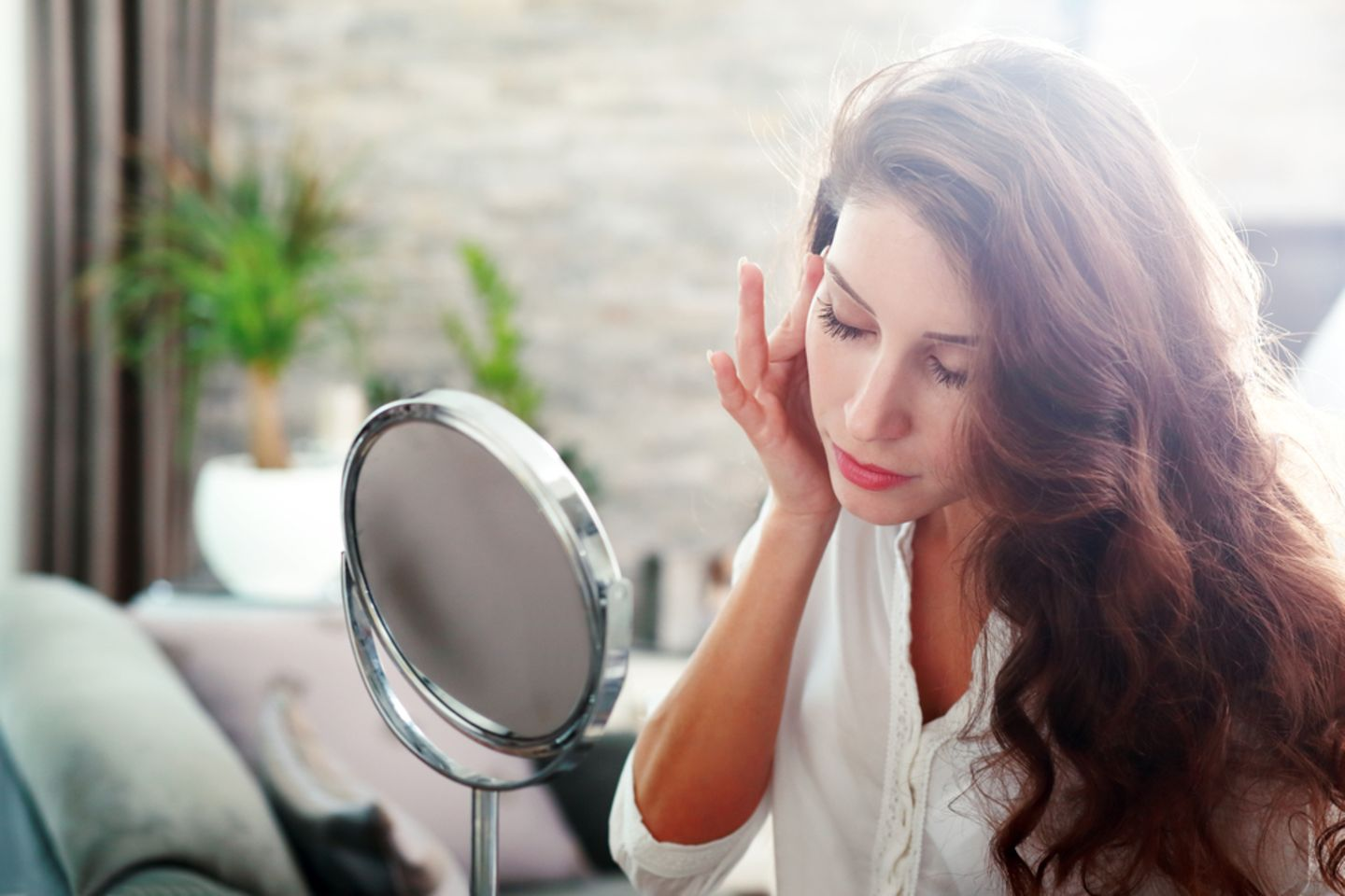 Pimples in the ear: woman grabs her right ear and looks in the direction of the mirror on a table
