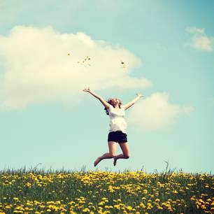 Horoskop: Eine Frau springt vor Freude in die Luft