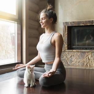 Horoskop: Eine Frau meditiert mit ihrer Katze