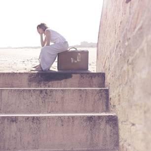 Frau sitzt auf Koffer