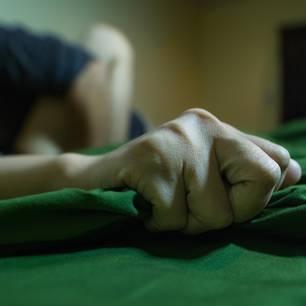 Samenerguss: Ein Mann beim Sex krallt sich ins Laken