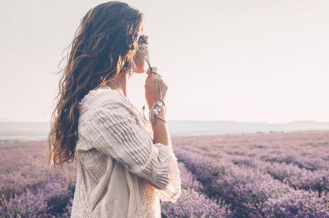 Boho-Cut: Junge Frau mit langem welligen Haar auf einem Lavendelfeld schaut in die Ferne