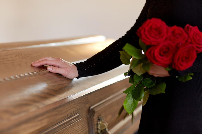 Trauernde Frau legt ihre Hand auf einen Sarg