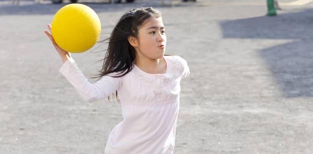 Völkerball: Dunkelhaariges Mädchen wirft gelben Ball
