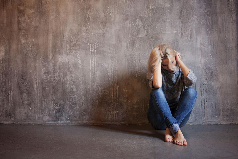 Michaela Muthig: Eine blonde junge Frau sitzt mit gesunkenem Kopf auf dem Boden an eine Wand gelehnt