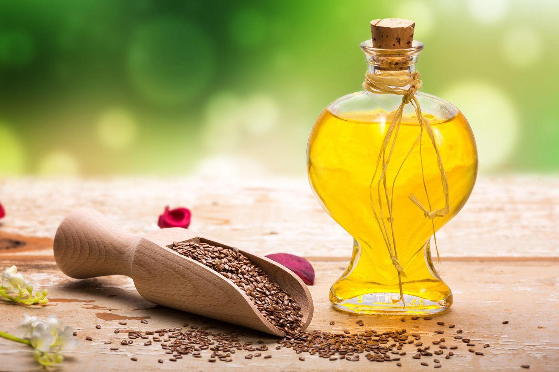 Wirkung von Leinöl: Leinöl in Flasche und Leinsamen daneben