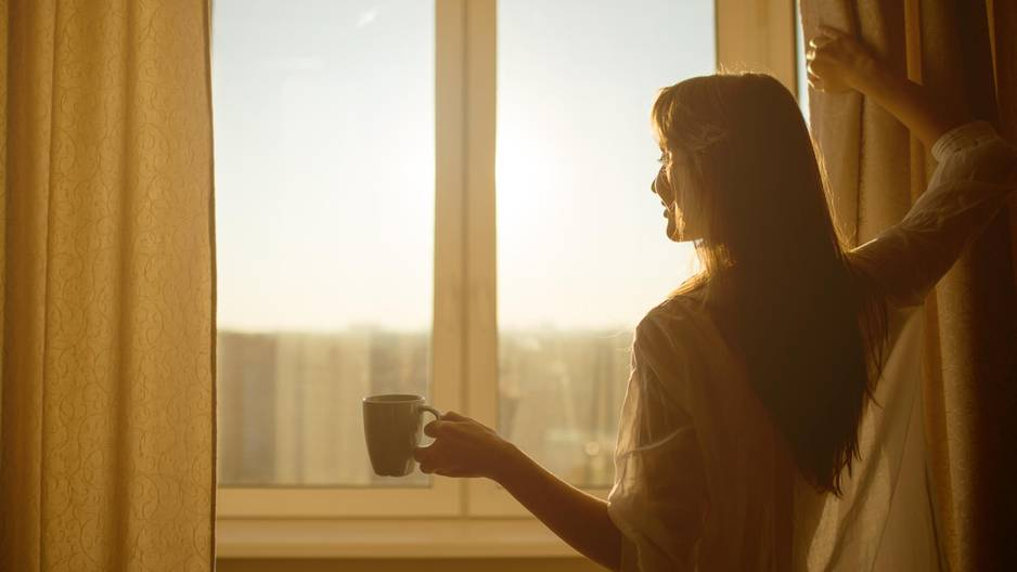 Frau steht im Sommer am Fenster