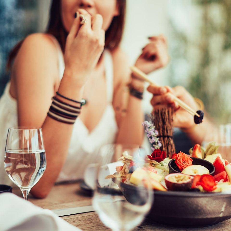 Vegane Ernährung: Frau isst in Restaurant