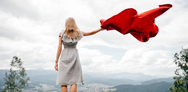 Dinge, für die man sich schlecht fühlt, obwohl sie gut sind: Eine Frau steht auf einem Hügel und hält ihre Jacke in den Wind
