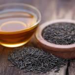 Wirkung von Schwarzkümmelöl: Öl neben Schale mit Schwarkümmelsamen
