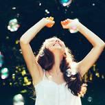 WOOP: Eine fröhliche Frau fängt Seifenblasen