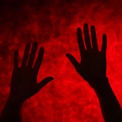 Blutvergiftung: Hände vor rotem Hintergrund