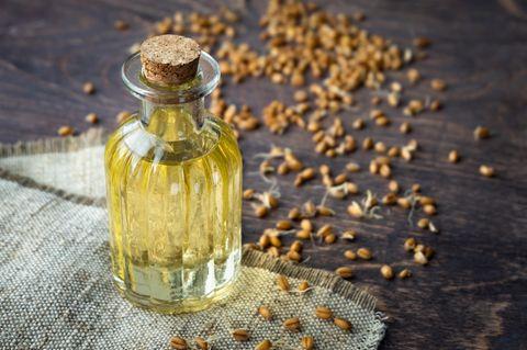 Weizenkeimöl: Flasche mit Öl steht auf einem Leinentuch, dahinter liegen Weizenkeime