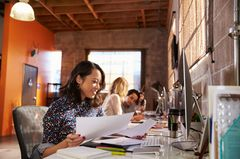 Konkurrenz im Job: Frau am Schreibtisch neben Kollegen