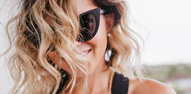 Frau mit Sonnenbrille und Haaren in Dialled-Up Blonde