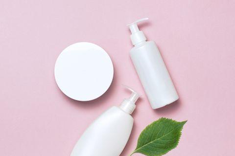 Haarwachs selber machen: Stylingprodukte liegen auf rosafarbenem Untergrund