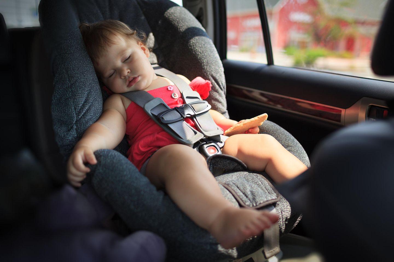 Ein Kind schläft im Auto.