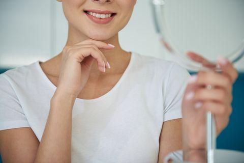 Pickel am Kinn: Frau hält einen Handspiegel und lächelt