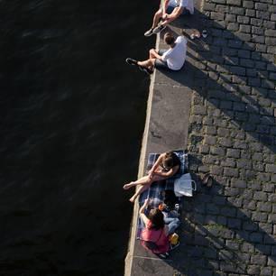 Horoskop: Zwei Frauen sitzen am Wasser und picknicken