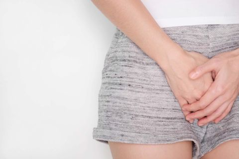 Vagina-Geruch: Frau hält die Hände vor den Unterleib