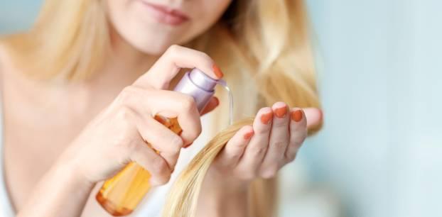 Arganöl für Haare: Frau gibt auf ihre langen Haare Öl