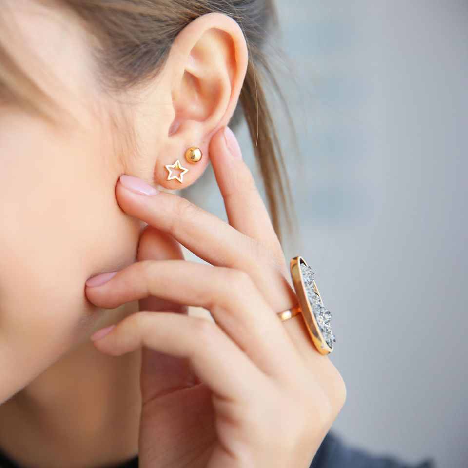Ohrenschmalz entfernen: Frau berührt ihr Ohr
