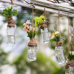 Gartendeko selber machen: Flaschen mit Blumen hängen von Gartentor