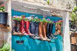 Gartendeko selber machen: Stiefel hängen über eine Tür und sind mit Pflanzen gefüllt