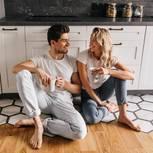 Worüber streiten glückliche Paare? Ein glückliches Paar sitzt in der Küche und schaut sich provokativ lächelnd an