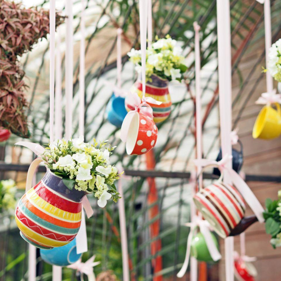 Gartendeko selber machen: Bunte Tassen und Kannen mit Pflanzen gefüllt hängen von der Decke