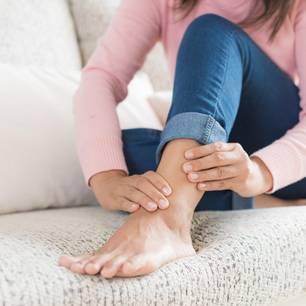 Wirkung von MSM: Frau fasst sich an Knöchel