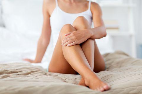 Depilation: Frau sitzt mit rasierten Beinen im Bett