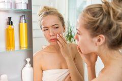 Verstopfte Talgdrüsen: Junge Frau guckt kritisch in den Spiegel und hält sich die Hand auf eine Stelle