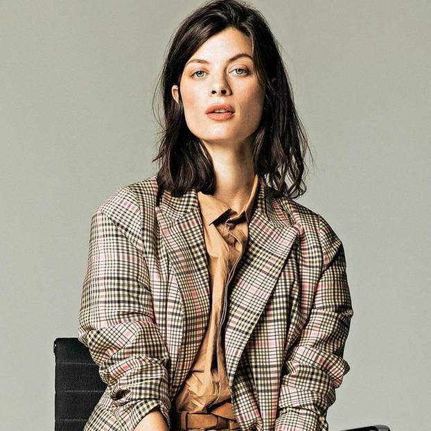Büro-Looks: Frau auf Bürostuhl in Overall und Blazer