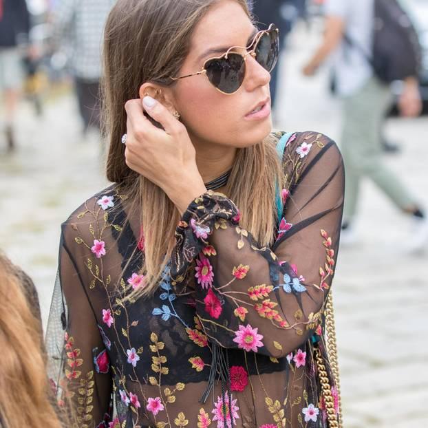Frau mit transparentem Oberteil mit floralen Stickereien