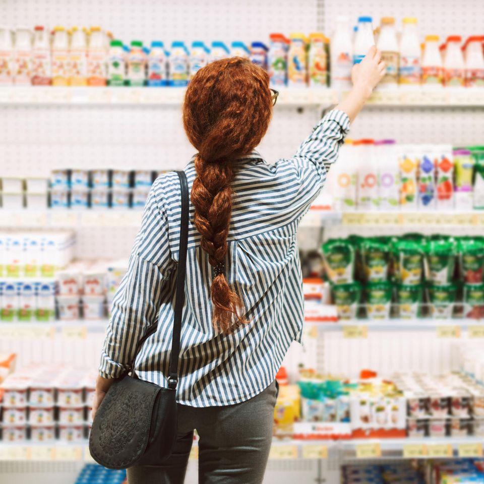 Musiktrick: Frau steht vor Supermarktregal und greift nach der Ware