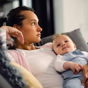 Witwenrente: Trauernde Frau mit Baby auf dem Arm
