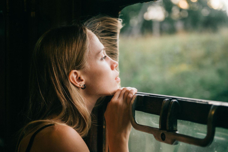 Sommerblues: Frau schaut traurig nach draußen