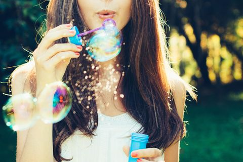 Seifenblasen selber machen: Frau pustet Seifenblasen
