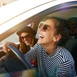 Worüber können nur selbstbewusste Menschen lachen? Zwei lachende Frauen im Auto